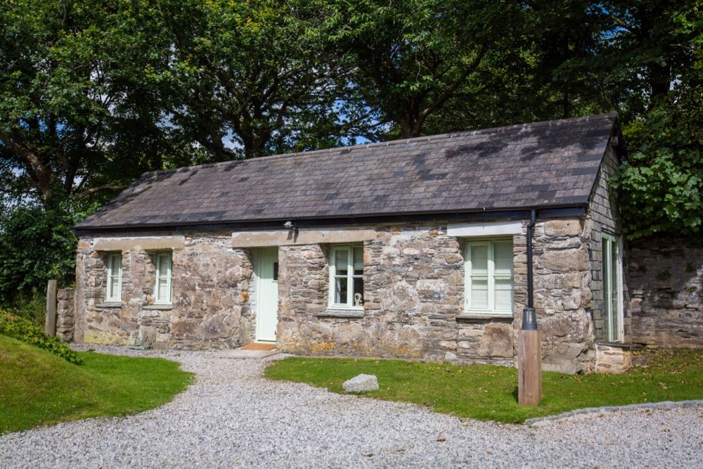 This is a photo of the exterior of cottage number one. Cottage number one sleeps two people. The proerty is single storey. The photo shows the full width of the cottage. In the background you can see trees which are in leaf. In the foreground you can see two patches of grass one on the left and one on the right and in the front there is gravel. The cottage is made of granite stone and is brown and grey in colour. The roof is constructed of grey slate and is pitched with the roof line running from left to right of the photograph along the length of the cottage. In the middle of the front of the cottage there is a wooden door that is painted pale green on either side of the story there are two windows on each side of this door. They are georgian style sash windows and also painted green. On the right hand side of the cottage the gable end has hanging slate on it. There is a French window in this end of the cottage and it is also painted green. In the foreground of the picture there is a light bollard for outside lighting.