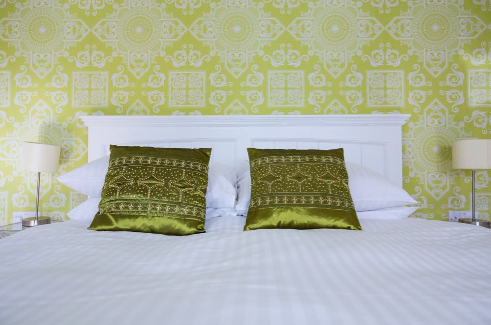 This picture shows a detail from the bedroom in cottage number one which is the small cottage that sleeps two people. The image shows the headboard and top part of a double bed. In the background there is some wallpaper and on each side of the bed there is a bedside lamp. The headboard is wooden and white. There are 2 pillows in white pillow cases on each side of the bed. The wall paper is lime green with an indian inspired white pattern. There are two scatter cushions one on each side. These are dark, lime green and are beaded in an indian pattern. The bedside lights are simple with cream shades and stainless steel stand. The duvet cover is white.