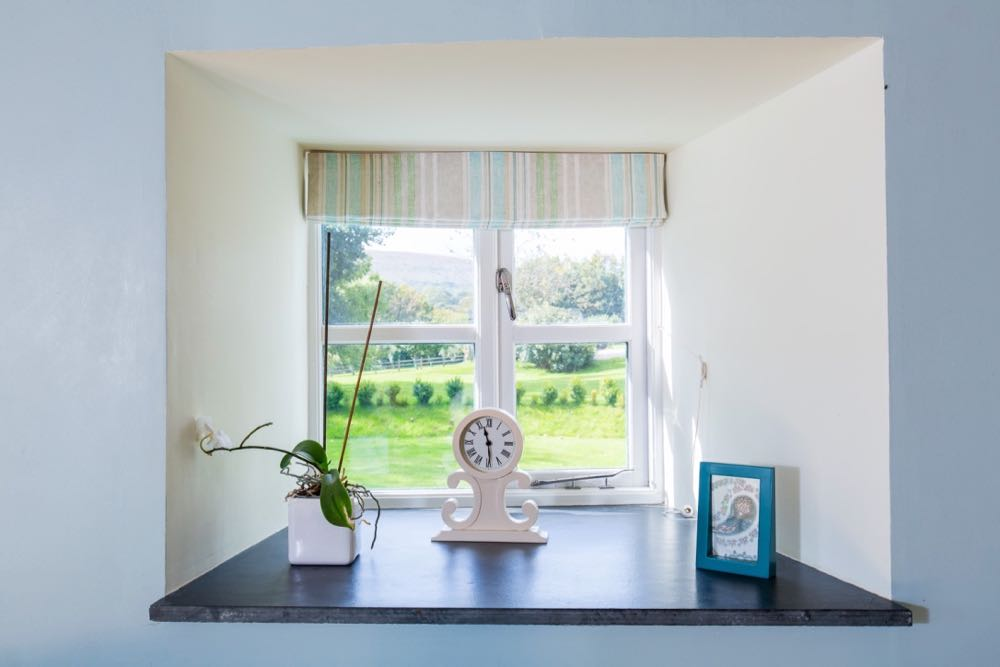 This image shows a detail of a window from cottage number two which sleeps 4 people. The image shows a windowin a wall which is painted blue. The reveals are painted cream and there is a slate windowsill. The window is a Georgian style four pain window. The window has a striped blind which is open. On the windowsill there is a potted orchid, a clock and a small blue frame with a paisley print in it. Outside the window you can see a distant hill, a lawn and a small box hedge.