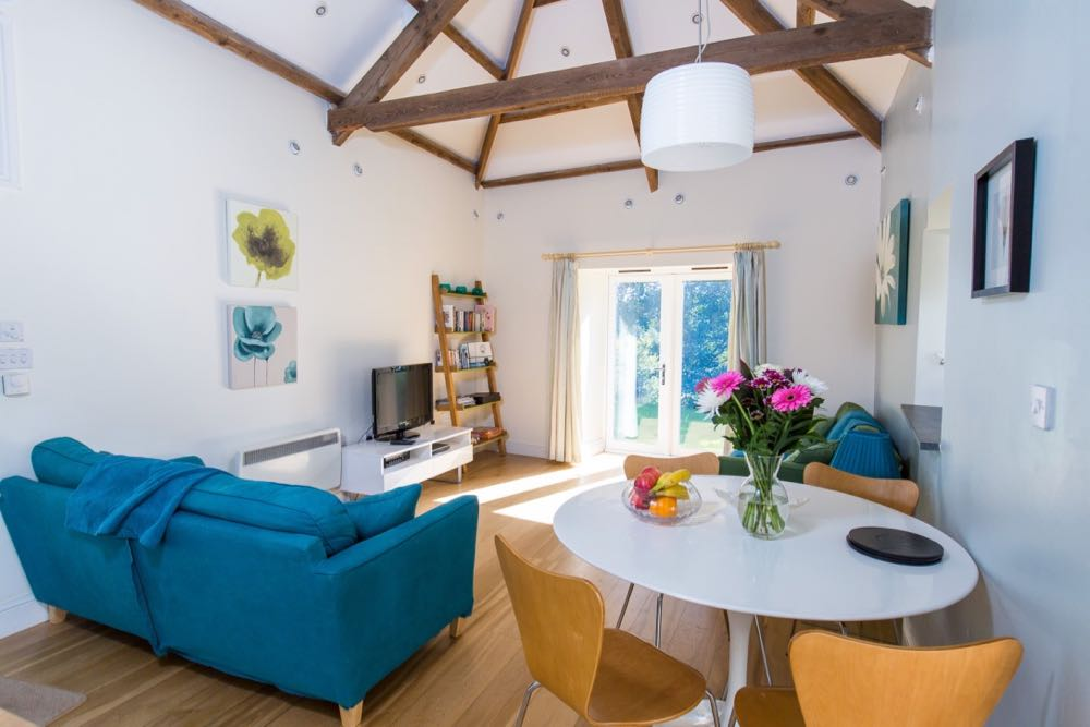 This image is of the lounge/dining area of cottage number two which is a sleeps four detached cottage. The room has oak flooring. There is a vaulted ceiling with many old oak a-frame beams supporting the roof. The walls are painted pale blue and the ceiling is white. There are spotlights in the roof and around the edge of the ceiling. There is a two seater blue sofa, a white TV table with a TV on top of it, a ladder shelving unit with five shelves. There is a second two seater sofa that is green. The dining area to the right of the photo has a round white pedestal table and four wooden dining chairs. On the dining table there is a vase of flowers and a bowl of fruit. On the wall to the left there are two prints one above the other line green and a blue floral design. There are two pictures on the right-hand wall one is blue with a floral design. There is a pendant light above the table.