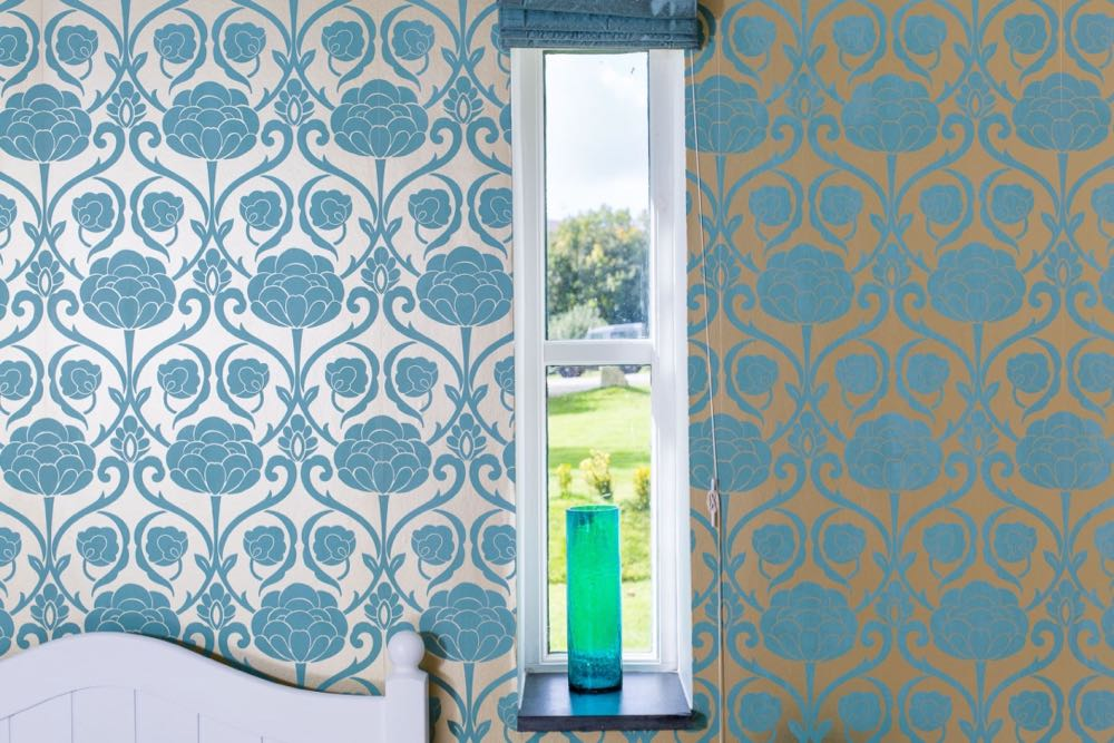 This image shows a detail of a window from cottage number two which sleeps 4 people. The image shows a window in a wall which has pale gold metallic wallpaper with a teal floral design. It is a long narrow window. There is a slate windowsill. The window has 2 panes. The window has a blue blind which is open. On the windowsill there is a teal, glass vase. Outside the window you can see some trees, a lawn and a small box hedge.