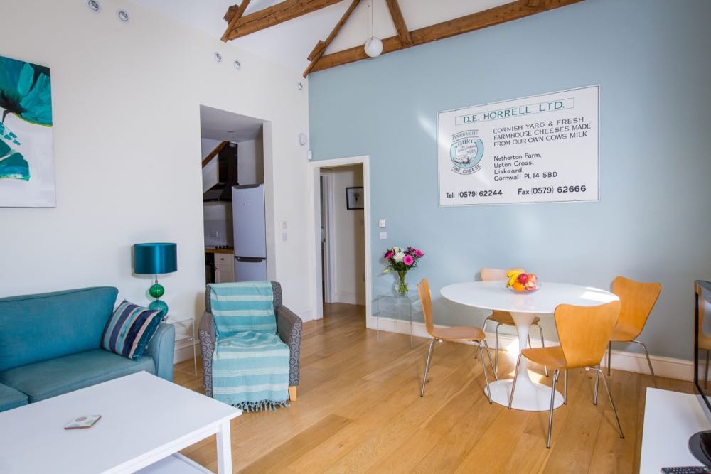 This is an image of the dining/lounge area in cottage number four which is a sleeps four cottage. The cottage has oak flooring. All the walls are painted cream. The ceiling is painted white. The wall in front of the camera is painted pale blue. There is a door on the left leading to a kitchen. There is a door to the right of that door leading into a corridor. There is an old advertising sign for the cheese farm on the blue painted wall. The sign is white with teal and black font. You can see the edge of 2 of the large, old, oak, a-frame beams which support the vaulted roof. In the middle of the photo you can see the the dining table which is white and round with a pedestal. There are 4 wooden dining room chairs. There are spotlights around the edge of ceiling. In the bottom right hand corner of the image you can see the corner of a white gloss TV unit made of walk. TTo the left of the table there is a glass table with a vase of pink and white flowers on it. There is a small, round, white pendant light in the corner of the room. There is a large picture with teal flowers on the wall on the left. There is a large teal sofa with a navy and teal striped cushion. There is a patterned grey and teal armchair with a teal and white striped throw. To the right of the sofa you can see a glass side table with a table lamp with a green and teal glass ball design and a teal shade. There is a white painted wooden coffee table in front of the sofa.