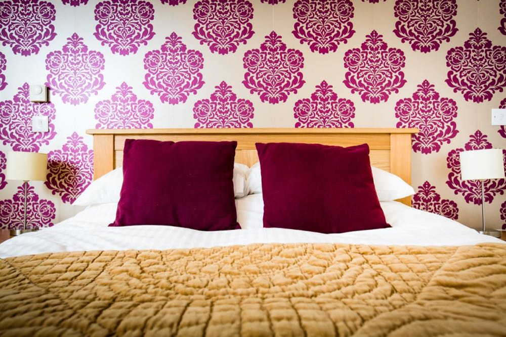 This is a detail shot of one of the double beds in cottage number five. Cottage number five sleeps six people. In this image you can see the wallpaper and the top of the bed. The wallpaper is gold with a red flock pattern. The pattern is quite bold. The bed frame is oak. The duvet cover and the pillows are white linen. There are two red cushions, one on each set of pillows. At the bottom of the bed there is a gold folded throw. On each side of the bed there is a bedside lamp which has a stainless steel base and a cream shade.