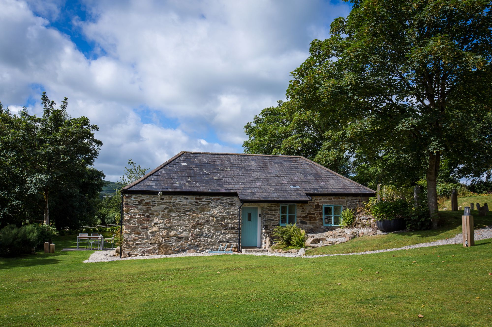 This picture shows cottage number two which is a detached cottage that sleeps 4 people. The cottage is in the middle of the image and there are lawns in front and a blue cloudy sky above. There are trees in leaf to the left and to the right. The cottage is built of local granite stone which is brown and grey in colour. It has a grey slate roof the main roof line runs from left to right along the length of the photograph. In the middle of the building there is the front doorthat is painted pale blue. On the right of the door there are 2 georgian style sash window also painted blue.